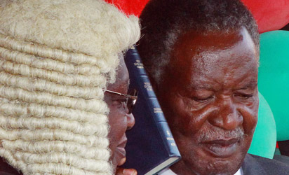 Zambia's President Michael Sata (R) takes oath during his swearing-in ceremony at the Supreme Court in Lusaka, on September 23, 2011. Sata took office today, kicking off with a pledge to crack down on the rampant corruption that turned voters away from his predecessor Rupiah Banda.    AFP PHOTO