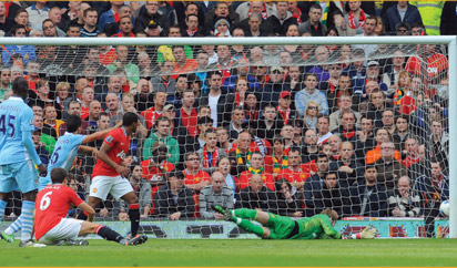 Manchester City's Italian striker Mario Balotelli (L) scores the opening goal past Manchester United's Spanish goalkeeper David De Gea (R) during the English Premier League football match between Manchester United and Manchester City at Old Trafford in Manchester, north-west England on October 23, 2011. AFP PHOTO