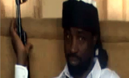 "Abubakar Shekau, the leader of Nigeria's Boko Haram Islamist militants, dressed in a black turban and a white gown and bullet-proof vest - holding an AK 47 rifle. In his 40-minute audio message, Shekau reportedly  blamed the deaths of ""innocent civilians"" on Nigeria's security forces but threatened to carry out a bombing campaign against Nigeria's secondary schools and universities - unless security forces stopped what he claimed was a series of recent attacks on Islamic schools or madrassas in the northern town of Maiduguri.AFP PHOTO / YOUTUBE"