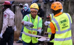 Members of a rescue team gathering personal belongings from victims of a Dana Air plane crash, which occurred on June 4th, at the site of the crash in the densely populated Toyin Area of Iju Ishaga in Lagos. Nigerian aviation authorities have suspended Dana Air's licence after a flight operated by the commercial passenger carrier crashed in Lagos, killing at least 159 people, a spokesman said on June 5. AFP PHOTO