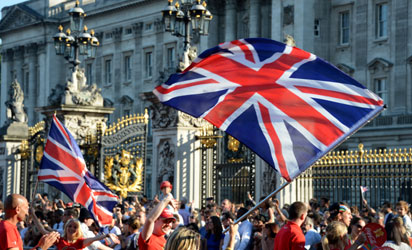 Dancers perform with the British national flag in front of the Buckingham Palace in London as the Olympic Flame is to arrive on July 26, 2012 for a torch relay on the eve of the 2012 London Olympic Games opening ceremony. AFP PHOTO