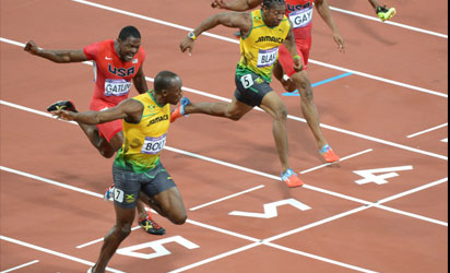 Jamaica's Usain Bolt (L) crosses the line to win the men's 100m final at the athletics event during the London 2012 Olympic Games on August 5, 2012 in London. AFP PHOTO