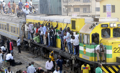 File photo: Passengers hanging on a moving train in Lagos at Ikeja Railway Station, Lagos...
