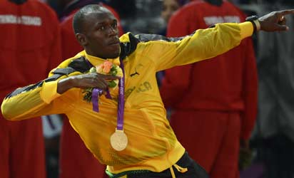 Jamaica's Usain Bolt poses on the podium with his gold medal after Jamaica won and set a new world record in the men's 4X100 relay final at the athletics event of the London 2012 Olympic Games on August 11, 2012 in London.    AFP PHOTO
