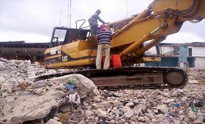 *A bulldozer at work during the demolition at Maza-Maza. INSET: A tipper being used to cart away debris from the scene
