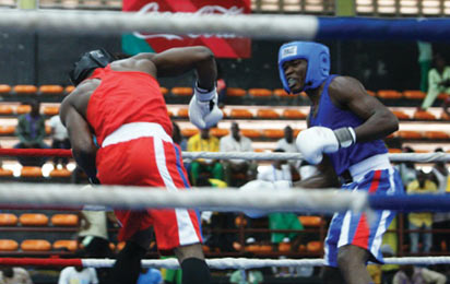 Rashidi Fatai of Ogun State (red) and Chinedu Ani of Imo State fight in the boxing 81kg men semi finals bout. Photo: Henry Unini