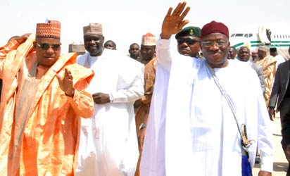 President Goodluck Jonathan (C, R), standing next to Borno State Governor Kashim Shettima (C, L) waves upon his arrival at Maiduguri international airport on March 7, 2013. Jonathan visits two cities in northeast Nigeria, where Islamist group Boko Haram has carried out scores of attacks, his first trip to the embattled region since taking office in 2010. AFP PHOTO