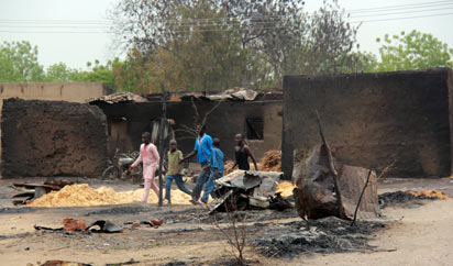 Residents walk past burnt houses in the remote northeast town of Baga on April 21, 2013 after two days of clashes between officers of the Joint Task Force and members of the Islamist sect Boko Haram on April 19 in the town near Lake Chad, 200 kms north of Maiduguri, in Borno State. Photo:AFP.