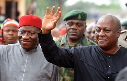 Ghanaian President John Mahama (R) waves to the crowd as he arrives accompanied by Nigerian President Goodluck Jonathan to attend the funeral service for writer Chinua Achebe at Ogidi, Anambra State.AFP PHOTO.