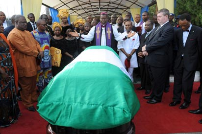 """Anglican priest Owen Nwokolo prays in front of the coffin bearing the body of late Nigerian writer Chinua Achebe upon arrival at Abuja airport, on May 21, 2013. The body of Achebe, the author of internationally acclaimed novel """"Things Fall Apart"""" and a towering figure in African literature, arrived in Abuja two months after his death in a US hospital. He is due to be buried in his native town of Ogidi on May 23, 2013. AFP PHOTO/PIUS UTOMI EKPEI"""