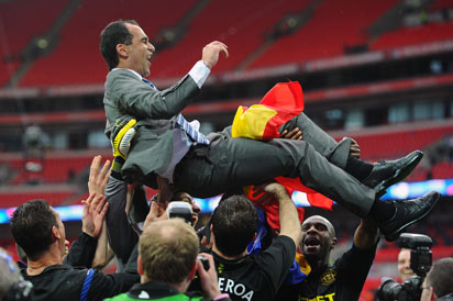 Wigan Athletic players hold aloft their Spanish manager Roberto Martinez (top) as they celebrate winning the English FA Cup final football match between Manchester City and Wigan Athletic at Wembley Stadium in London on May 11, 2013. AFP Photo: