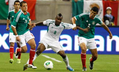 HOUSTON - MAY 31: Aide Brown Ideye #8 of Nigeria fends off Javier Hernandez #14 and Francisco Rodiriguez #2 of Mexico as he attmpts to gain control of the ball at Reliant Stadium on May 31, 2013 in Houston, Texas. /AFP