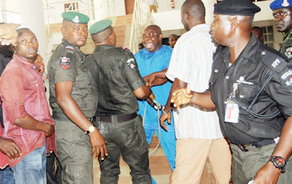 Hon Evan Bapakaye at Loggerheads with a Mobile Police Officer at the Rivers State House of Assembly during the Crisis that Rocked the House.  Photo: Nwankpa Chijioke