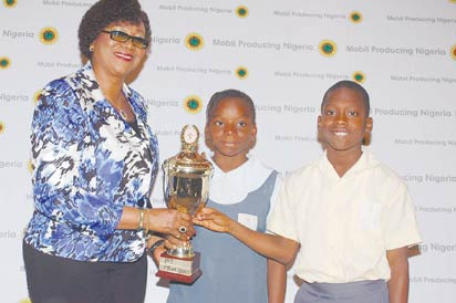 Mrs Regina Udobong, Adviser, Public and Government Affairs, Mobil Producing Nigeria, presenting a trophy to Owodeha Ashaka and Eyehova Ejiroghene of Delta State, winners of the Primary School Quiz category at the 2013 MPN/STAN National Science Quiz competition, in Uyo, Akwa Ibom State.
