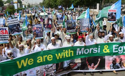 Pakistani supporters of Islamic party Jammat-e-Islami (JI) carry placards as they march behind a banner during a protest in Karachi on August 16, 2013, against the bloody Egyptian military crackdown on supporters of ousted president Mohamed Morsi in Cairo. AFP PHOTO