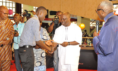 *Delta State Governor, Dr. Emmanuel Uduaghan (2nd r) handing over a scholarship award to one of the recepients while CAN president, Pastor Ayo Oritsejafor (r), Prof. Gabriel Yomere (l) and others look on.