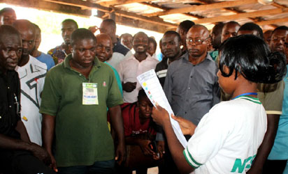 Corper Shobowale Ibironke, Presiding officer, Awka South ward 001 counting result before party agents and voters after voting.
