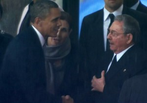 A screengrab taken from the South African Broadcasting Corporation live feed shows US President Barack Obama (L) shaking hands with Cuban leader Raul Castro as he arrives for the memorial service for late South African President Nelson Mandela at Soccer City Stadium in Johannesburg on December 10, 2013.AFP PHOTO