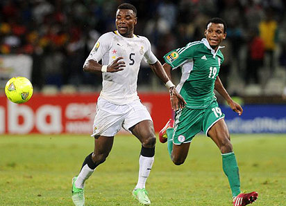 GRITTY. . . Super Eagles' Abdullahi Shehu ( R ) vies with Black Stars of Ghana's Samuel Ainooson during their semi final match of the 2014 CHAN in South Africa.