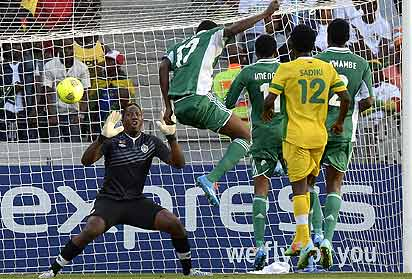 *POINT BLANK.......Super Eagles' Chinoso Obiozor (C) scores  against Zimbabwe's goalie George Chigova during the third place match of CHAN on February 1. PHOTO: AFP