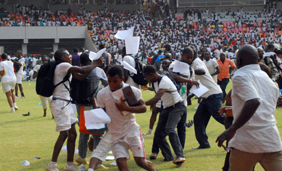 NIGERIA, Abuja : Job-seekers applying for work at the Nigerian immigration department scramble as their exam papers fly in the air, on the pitch of Abuja National Stadium, on March 15, 2014. AFP PHOTO