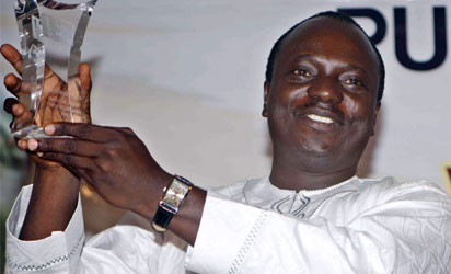 "NIGERIA, Lagos : Nigerian poet Tade Ipadeola holds up his trophy after he won the prestigious Nigeria Prize for Literature during a ceremony in Lagos on March 6, 2014. Ipadeola's ""The Sahara Testaments"" won the most lucrative writing award in Africa - $100,000, the Nigeria Prize for Literature, for his account of the history and culture of the world's largest desert. AFP PHOTO"