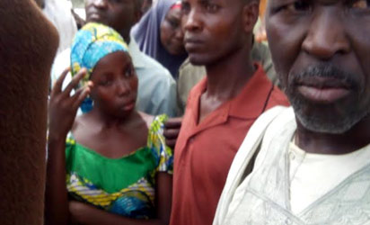 One of the lucky abducted students in Chibok who was later rescued and being handed over by her parents at school premises on Monday. Photo by Ndahi Maiduguri.