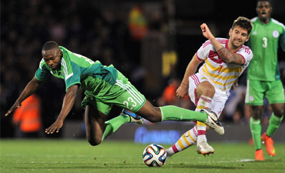UNITED KINGDOM, London : Nigeria's striker Shola Ameobi (L) vies with Scotland's defender Charlie Mulgrew (R) during the international friendly football match between Nigeria and Scotland at Craven Cottage in London on May 28, 2014, ahead of the FIFA World Cup . AFP PHOTO