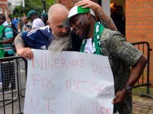 THE PATRIOT . . . A Nigeria fan holding a placard is embraced by a Scotland fan before kick off