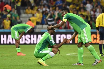 Nigeria's Nigeria's midfielder John Obi Mikel and Nigeria's defender Joseph Yobo (R) shake hands at the end of Group F football match between Iran and Nigeria at the Baixada Arena in Curitiba at the 2014 FIFA World Cup on June 16, 2014. AFP PHOTO / LUIS ACOSTA