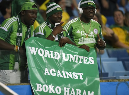 """Nigeria's fans hold a banner reading """"World Unites Against Boko Haram"""" before the Group F football match between Nigeria and Bosnia-Hercegovina at the Pantanal Arena in Cuiaba during the 2014 FIFA World Cup on June 21, 2014. AFP PHOTO"""