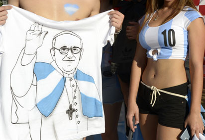 Argentinean supporters pose with a t-shirt featuring a picture of Pope Francis outside of the Maracana Stadium in Rio de Janeiro, on June 15, 2014 before the start of the 2014 FIFA World Cup Group F football match between Argentina and Bosnia-Herzegovina.  AFP PHOTO / Juan Mabromata