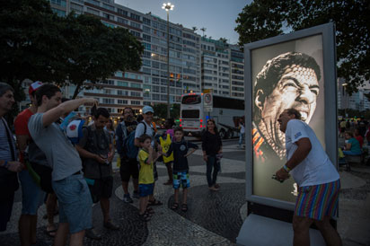 Tourists joke in front of an advertisement with the portrait of Uruguay's forward Luis Suarez at Copacabana beach in Rio de Janeiro, Brazil, on June 26, 2014. Sportswear giant Adidas said Thursday it would stop using Luis Suarez, one of its key promotional stars, for World Cup adverts after his four-month ban from football activities for biting Italian Giorgio Chiellini. AFP PHOTO / YASUYOSHI CHIBA