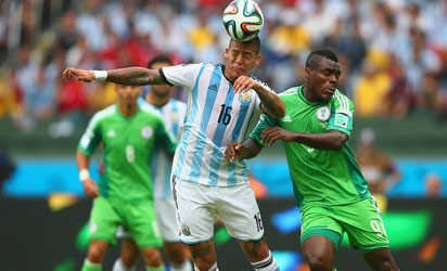Marcos Rojo of Argentina goes for a header against Emmanuel Emenike of Nigeria during the 2014 FIFA World Cup Brazil Group F match between Nigeria and Argentina at Estadio Beira-Rio on June 25, 2014 in Porto Alegre, Brazil. (FIFA)