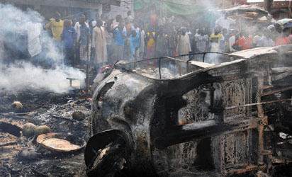 Maiduguri : People gather to look at a burnt vehicle following a bomb explosion that rocked the busiest roundabout near the crowded Monday Market in Maiduguri, Borno State, on July 1, 2014. A truck exploded in a huge fireball killing at least 15 people on July 1 in the northeast Nigerian city of Maiduguri, the latest attack in a city repeatedly hit by Boko Haram Islamists. AFP PHOTO