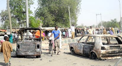 People gather to look at a burnt vehicle  following a bomb explosion that rocked the busiest roundabout near the crowded Monday Market in Maiduguri, Borno State, on July 1, 2014. A truck exploded in a huge fireball killing at least 15 people on July 1 in the northeast Nigerian city of Maiduguri, the latest attack in a city repeatedly hit by Boko Haram Islamists.  AFP PHOTO