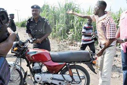 A Policeman seizing a motorcycle from the owner, in Lagos.