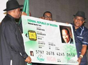 PRESIDENT GOODLUCK JONATHAN (L), DISPLAYING A DUMMY OF HIS NATIONAL IDENTITY CARD AT THE LAUNCH OF e-ID CARD IN ABUJA ON THURSDAY (28/8/14). WITH HIM ARE MINISTER OF AGRICULTURE, DR AKINWUMI ADESINA AND BOARD CHAIRMAN, NATIONAL IDENTITY MANAGEMENT COMMISSION, PRINCE UCHE SECONDUS. BJO/NAN -