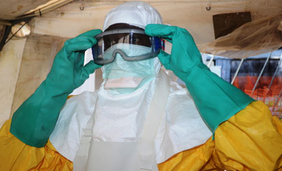 A file photo taken on June 28, 2014 shows a member of Doctors Without Borders (MSF) putting on protective gear at the isolation ward of the Donka Hospital in Conakry, where people infected with the Ebola virus are being treated. Guinea announced on August 9, 2014 it was closing its land borders with Liberia, Sierra Leone over Ebola fears.    AFP PHOTO