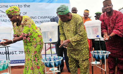 FROM LEFT: MINISTER OF WATER RESOURCES, MRS SARAH OCHEPE; CHAIRMAN, MINI BUS UTAKO PARK, ABUJA, MR OLUGBADE  OLAGUNJU AND FCT  DEPUTY CHAIRMAN, NATIONAL UNION OF ROAD TRANSPORT WORKERS,  ALHAJI GABI IBRAHAM, WASHING  THEIR HANDS TO COMMENCE THE NATIONAL EMERGENCY HANDS WASHING CAMPAIGN TO PREVENT THE SPREAD  OF EBOLA VIRUS IN NIGERIA AT UTAKO  MOTOR PARK IN  ABUJA ON MONDAY