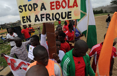 """Players of the ''FC Gberedou Abobo"""" football team poses with a sign reading ''Stop ebola in Africa"""" prior to a football tournament gathering youth from Guinea near the Koumassi sports center in Abidjan on August 10, 2014. West Africa was counting the cost of measures to contain the deadly Ebola epidemic on August 10, as unprecedented restrictions caused snarled transport, food shortages and soaring prices.  AFP PHOTO"""