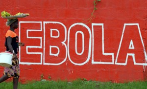 "A seller of bananas walks past a slogan painted on a wall reading ""Ebola"" in Monrovia on August 31, 2014. Liberia on August 30, 2014 said it would deny permission for any crew to disembark from ships at the country's four seaports until the Ebola epidemic ravaging west Africa was under control. AFP PHOTO"