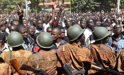 A crowd gathers on October 31, 2014 in front of army headquarters in Ouagadougou, demanding that the army take over following the resignation of the president. Burkina Faso's army chief Navere Honore Traore said he was taking power on October 31 as head of state after President Blaise Compaore announced his resignation as tens of thousands of protesters demanded that he quit immediately after a day of unrest that saw mass protests and the storming of parliament and other public buildings.    AFP PHOTO