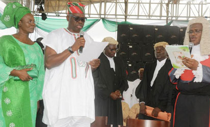Gov. Ayo Fayose of Ekiti taking Oath of Office before Chief Judge of Ekiti, Justice Ayodeji Daramola, at the inauguration in Ado-Ekiti On Thursday with them is Mrs Feyisetan Fayose.