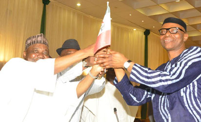 .VICE PRESIDENT NAMADI SAMBO (L), PRESENTING PDP FLAG TO GOV. OLUSEGUN MIMIKO OF ONDO STATE,  WHO DEFECTED TO THE PARTY  IN ABUJA ON THURSDAY (2/10/14).