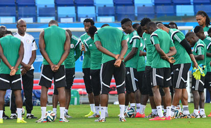 HUMBLED: Super Eagles players listen to their coach before training ahead of the return clash with Sudan on Wednesday.