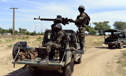 Cameroonian soldiers patrol on November 12, 2014 in Amchide, northern Cameroon, 1 km from Nigeria. The city was raided by Islamists from Nigeria's Boko Haram, killing eight cameroonian soldiers and leading the population to flee on October 15, 2014, before another six coordinated attacks that killed at least three civilians in the remote north of the country, on November 9, 2014. Boko Haram's five-year insurgency in neighboring Nigeria has left thousands dead, and the Islamists have occasionally carried out attacks over the border. Cameroon has deployed more than 1,000 soldiers in the extreme northeast of the country to counter the Islamist threat. AFP PHOTO