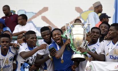 Enyimba players celebrate with Federation Cup at the Teslim Balogun Stadium in Lagos on November 23, 2014. Two-time African champions Enyimba on Sunday retained the Nigeria FA Cup after beating Dolphins 2-1 at the Teslim Balogun Stadium in Lagos. It was Enyimba's fourth cup triumph after they also won in 2005, 2009 and 2013. However, the Aba club will represent Nigeria in next year's CAF Champions League after they finished as runners-up in the league,  while beaten finalists Dolphins will feature in the CAF Confederation Cup. AFP PHOTO