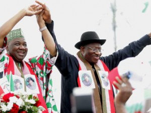Nigerian President Goodluck Jonathan (R) and Nigerian Vice President Namadi Sambo greet supporters at a ceremony in Abuja on November 11, 2014. Nigeria's President Goodluck Jonathan on November 11 declared his bid for re-election, vowing to finally defeat Boko Haram whose rise in strength during his first term has threatened the country's sovereignty. The 56-year-old made the announcement to tens of thousands of supporters in the red, white and green of his ruling Peoples Democratic Party (PDP), at a carefully orchestrated ceremony including patriotic music, dancing, prayers and speeches. AFP PHOTO