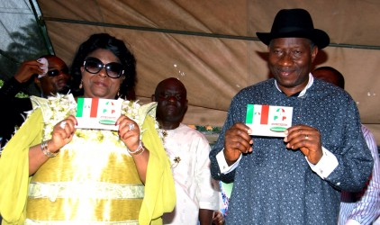 PRESIDENT GOODLUCK JONATHAN AND THE FIRST LADY DR(DAME) PATIENCE JONATHAN  DISPLAY THEIR NEW PDP MEMBERSHIP CARD AT THE OTUABULA 11,   WARD 13 PDP WARD CONTRESS IN OGBIA  LOCAL GOVERNMENT OF BAYELSA STATE